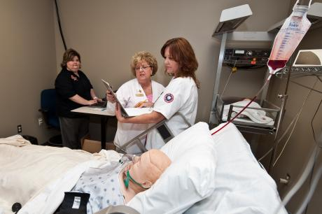 Nursing Professor Gina Seratt instructs student on patient care
