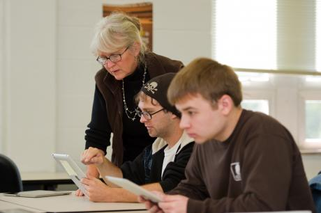 Professor Linda Weeks working with students using tablets