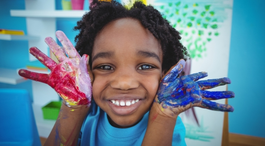Happy child smiling with paint on hands