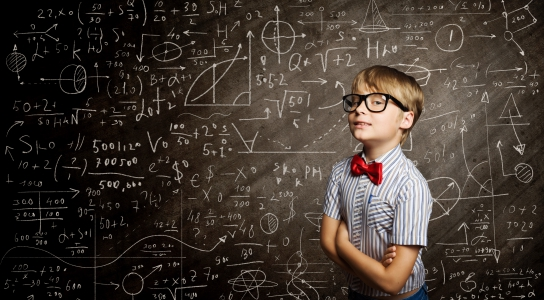 7 year old boy in black glasses with a red bow tie looking smart standing in front of a blackboard filled with mathatical equations.
